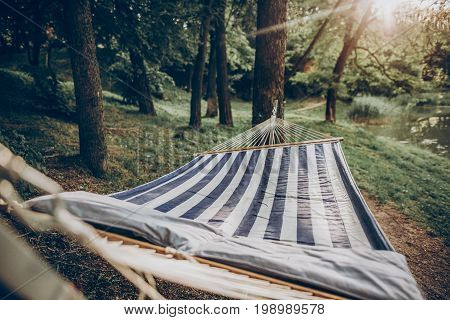 Stylish Striped Hammock Hanging Outdoors At Nature Resort Close-up, Blue And White Stipes On Comfort