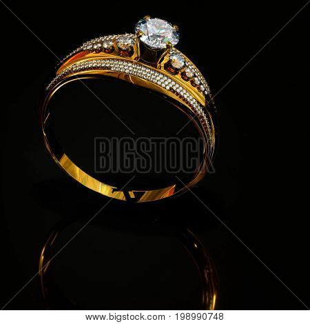 Gold ring with diamond gem jewelry. Luxury jewellery bijouterie with crystal gemstone for people in love. Surface reflection under ring on black background. 3D rendering