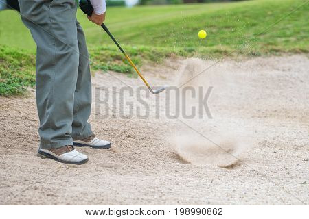 Golfer hitting out of a sand trap, The golf course is on the sand, Sand making splashes, Sun and sunshine in the background
