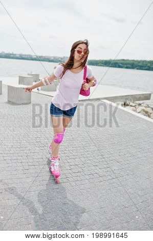 Portrait Of A Good-looking Young Woman In Casual Clothing Rollerblading On The Pavement In The Park.