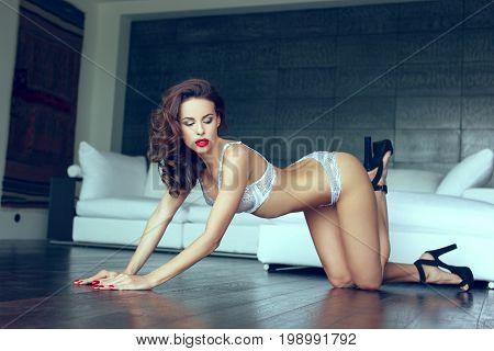 Sexy woman in white underwear posing on floor indoor