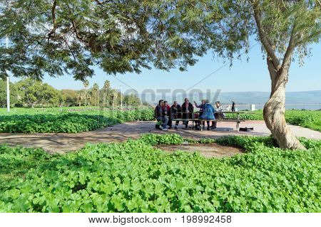 Israel. - February 17.2017. A group of pilgrims rests on the shore of the Sea of Galilee.