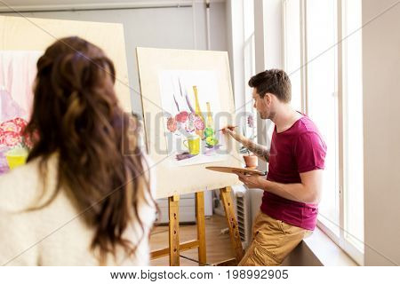 creativity, education and people concept - artists or students with palettes and paint brushes painting still life picture on easels at art school studio