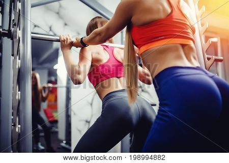 European girl in a gym with long hair is engaged with a personal trainer on the simulator bar for squatting. Concept training under the guidance of a mentor, group exercise in sports.