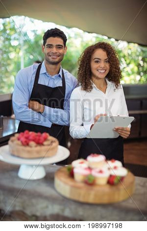 Male waiter and female waitress with clipboard at outdoor restaurant