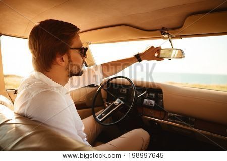 Young handsome man in sunglasses sitting inside his car and adjusting rear view mirror
