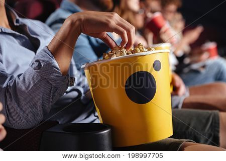 Cropped picture of young man sitting in cinema watch film eating popcorn.