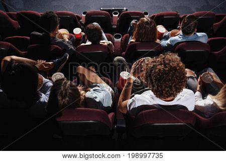 Image of friends sitting in cinema watch film eating popcorn and drinking aerated sweet water.