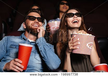 Image of happy friends sitting in cinema watch film eating popcorn and drinking aerated sweet water.