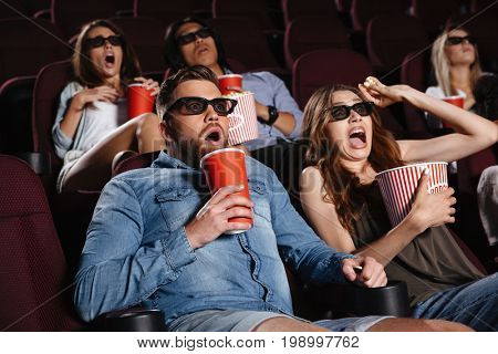 Photo of shocked friends sitting in cinema watch film eating popcorn and drinking aerated sweet water.