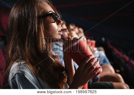 Image of young lady sitting in cinema watch film drinking aerated sweet water.