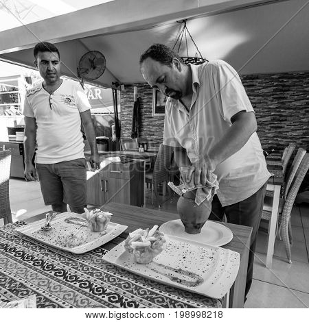 SIDE TURKEY - JULY 07 2015: The restaurant in Side the waiter served the meat from the clay pot. Black and white.