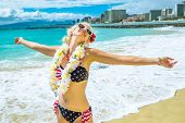 Happy female showing her her hawaiian lei necklace. Freedom woman with american flag bikini and white garland orchids in Hawaii. Waikiki Beach in Honolulu, Oahu. Tropical destination holiday travel. poster