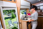 Woman cooking in camper, motorhome interior. Family vacation travel, holiday trip in motorhome, Caravan car Vacation. poster