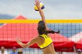 Volleyball player is a female beach volleyball player jumping at the net to spike the ball down. poster