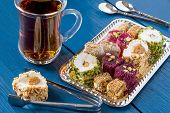 Eastern sweets. Assorted traditional Turkish delight (Rahat lokum) on blue wooden background. Turkish delight with different nuts and coconut shavings tea in glass (armud) tongs for sweets spoons poster