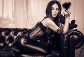 A sexy woman in leather pants and a corset erotically sits on the couch. Sensual girl in leather clothes posing on leather sofa. Vintage tinting poster