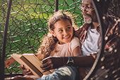 smiling african american granddaughter reading book while sitting in swinging hanging chair with grandfather poster