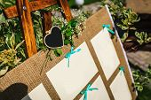 Wedding seating chart on the easel in the park. Close-up image. Outdoors. Copy space poster