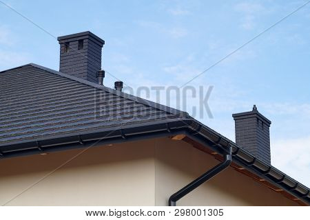 A Newly Built Residential House. A Fragment Of The Roof Made Of Metal Roof Tiles, New Chimneys.