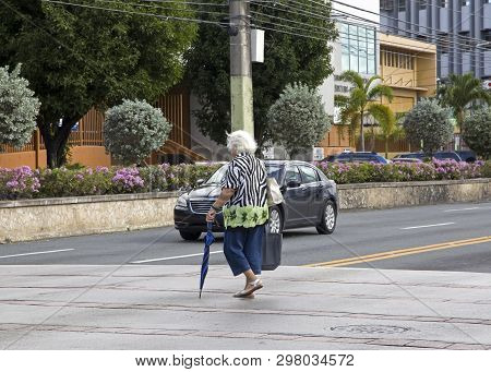 Bayamon/puerto Rico - February 26, 2019: Elderly Woman Crosses Street With Umbrella.