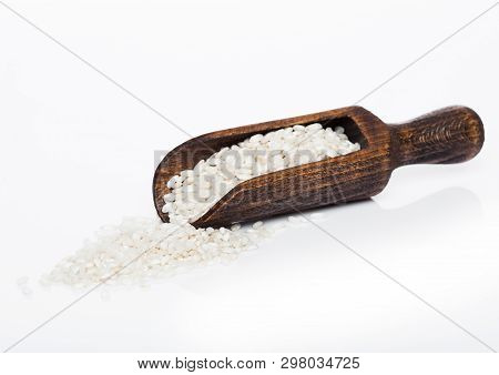Wooden Spoon Of Raw Organic Arborio Risotto Rice On White Background.