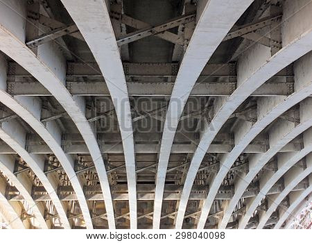Perspective View Of Curved Arch Shaped Steel Girders Under An Old Road Bridge With Rivets And Struts