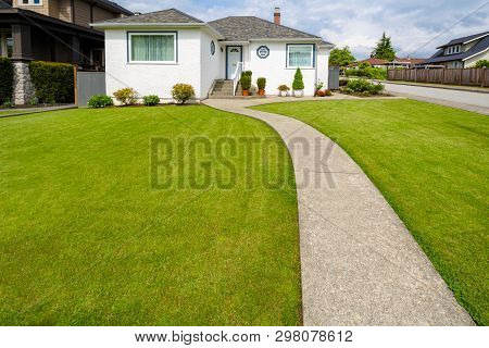 Main Entrance Of Small Residential House With Concrete Walkway Over Green Lawn Of Front Yard. Family