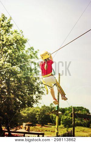 Little Brave Caucasian Girl Using A Zip Line.