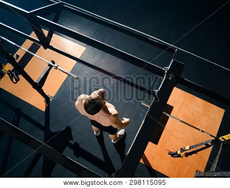 Young Sportsman Preparing for Exercises on the Horizontal Bar in the Modern Functional Gym. Fitness and Healthy Lifestyle Concept. View from the Top