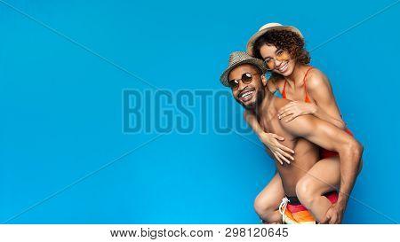 Happy Black Boyfriend Piggybacking His Cheerful Girlfriend, Both Wearing Swimsuits, Blue Panorama Ba