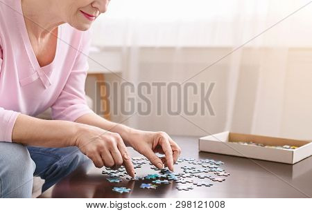 Alzheimers Disease And Dementia Prevention. Senior Woman Playing Jigsaw Puzzle On Wooden Table At Ho