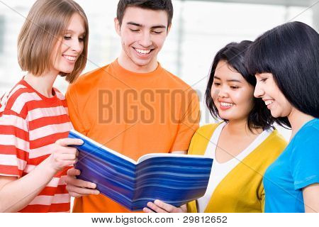 Happy students looking at book