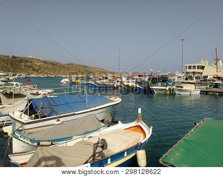 Mgarr, Harbor,gozo, Malta - Fishing Boats Await Their Owners At The Mgarr Village Harbor, On The Mal
