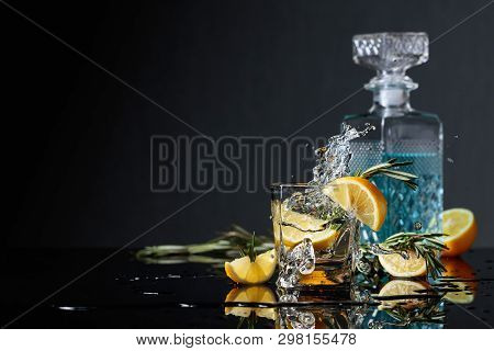 Gin-tonic With Lemon Slices And Twigs Of Rosemary On A Black Reflective Background. Lemon Slice Fall