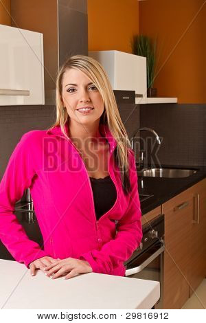Attractive woman in kitchen with glass of orange juice