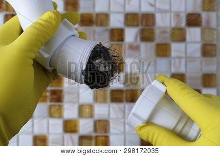 Elimination Of Blockage In Sewer Pipes. Hands In Yellow Gloves Disassemble And Clean The Sink Siphon
