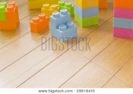 Colorful toy blocks on wooden floor.