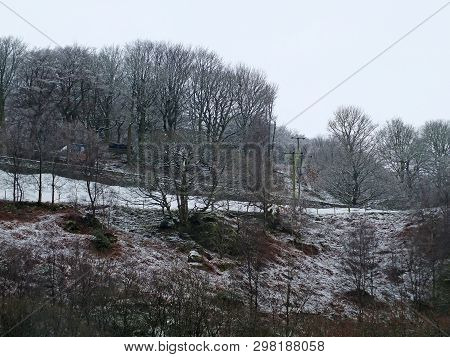 Snow Scene With Ice On Frozen Forest Trees And Hillside Fields With A Stone Wall Bordering A Country