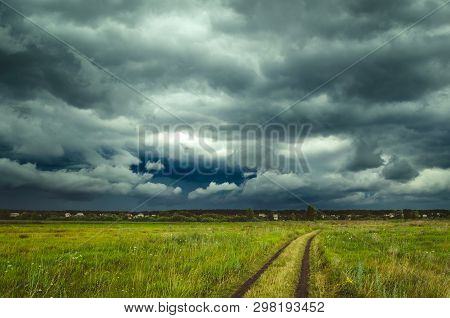 Dark Rain Storm Clouds Over The Field.