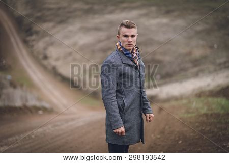 Masculine Attractive Young Male In The Park Or Field Or Track. Handsome Man In Grey Coat And Blue Sc