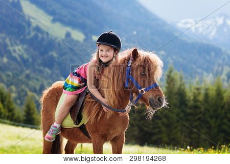 Kids Riding Pony In The Alps Mountains. Family Spring Vacation On Horse Ranch In Austria, Tirol. Chi