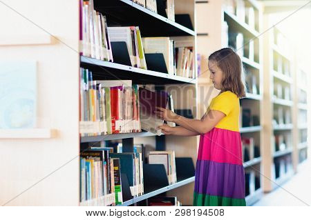 Child In School Library. Kids Read Books. Little Girl And Boy Reading And Studying. Children At Book