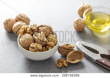 Bowl With Whole And Peeled Walnut Kernels And Glass Dish With Walnut Oil. Healthy Food For Brain. Fr