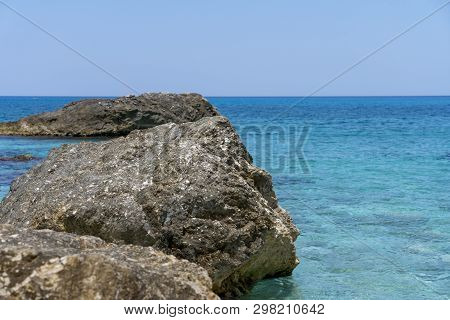 Some Rocks In The Sea, With Clear Blue Sky