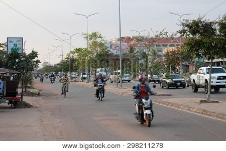 Siem Reap, Cambodia, December 17, 2018 People On Mopeds Ride On A City Street. Typical Traffic In An