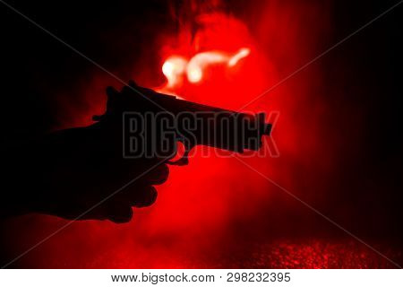 Male Hand Holding Gun On Black Background With Smoke Toned Back Lights