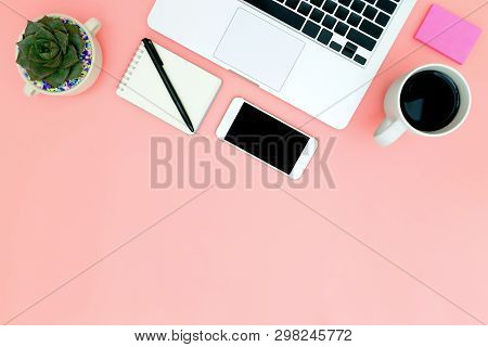 Flat Lay Office Workspace With Blank Laptop, Clipboard, Eucalyptus Branches On Pink Background. Top