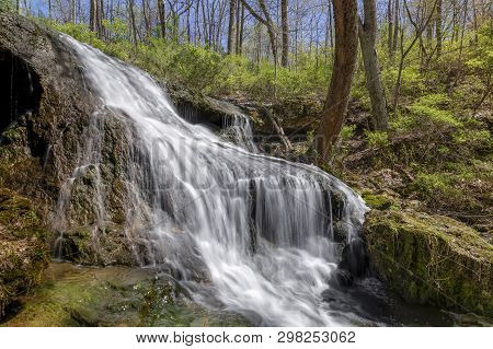 A Waterfall Cascades Down A Rocky Slope On A Sunny Day In George Rogers Clark Park Near Springfield,