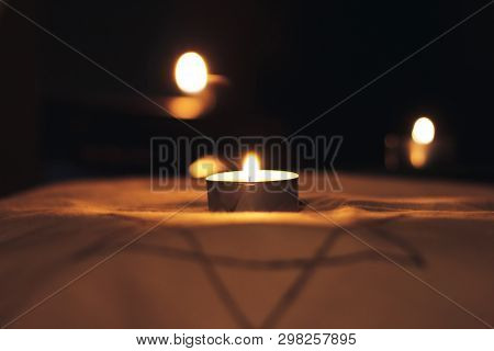 Candles Burning Over The Star Of David In Memory Of The Dead.